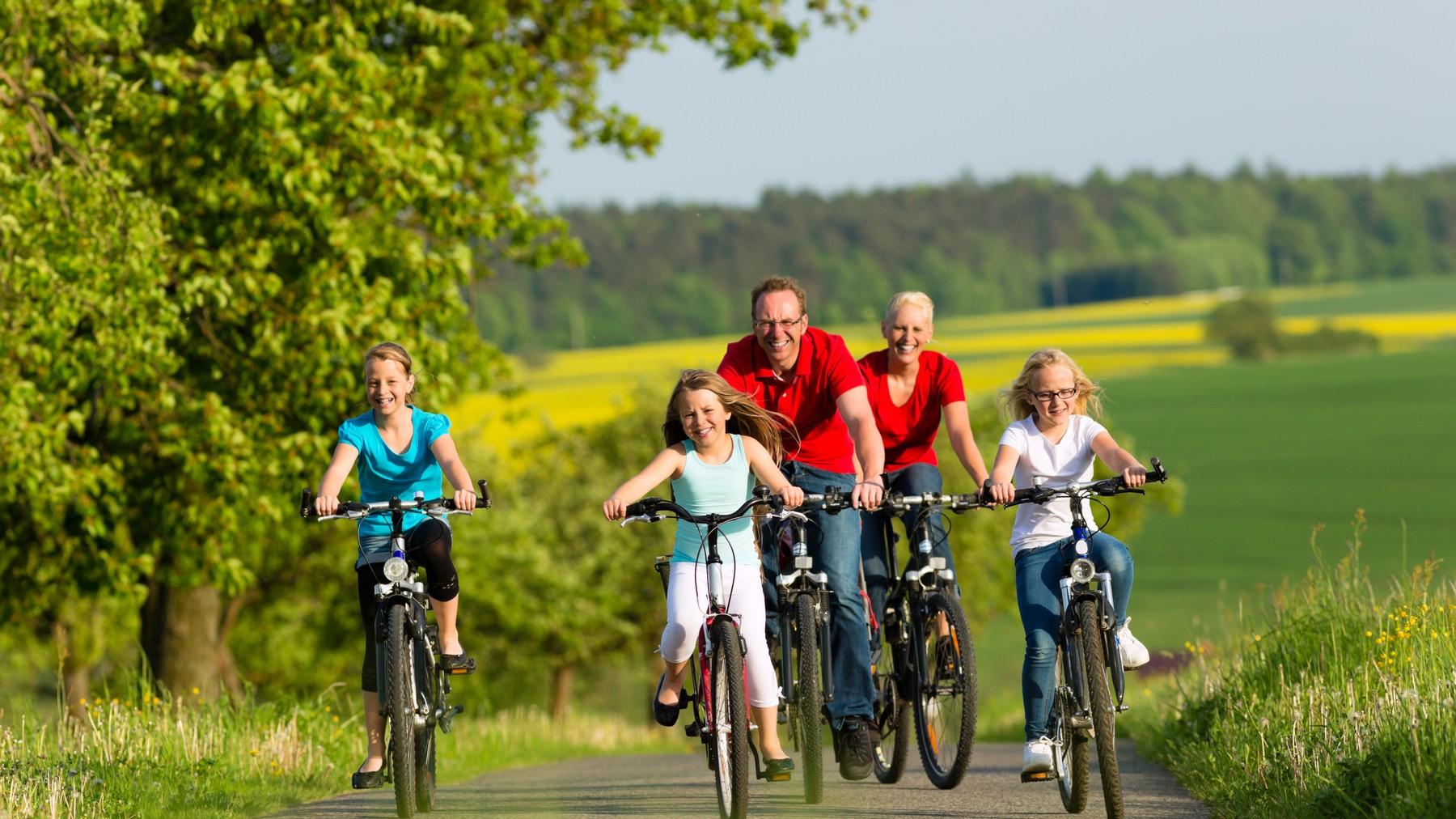 พ่อแม่กับลูกสาวทั้งสามคนปั่นจักรยานด้วยกันในสวนสีเขียว