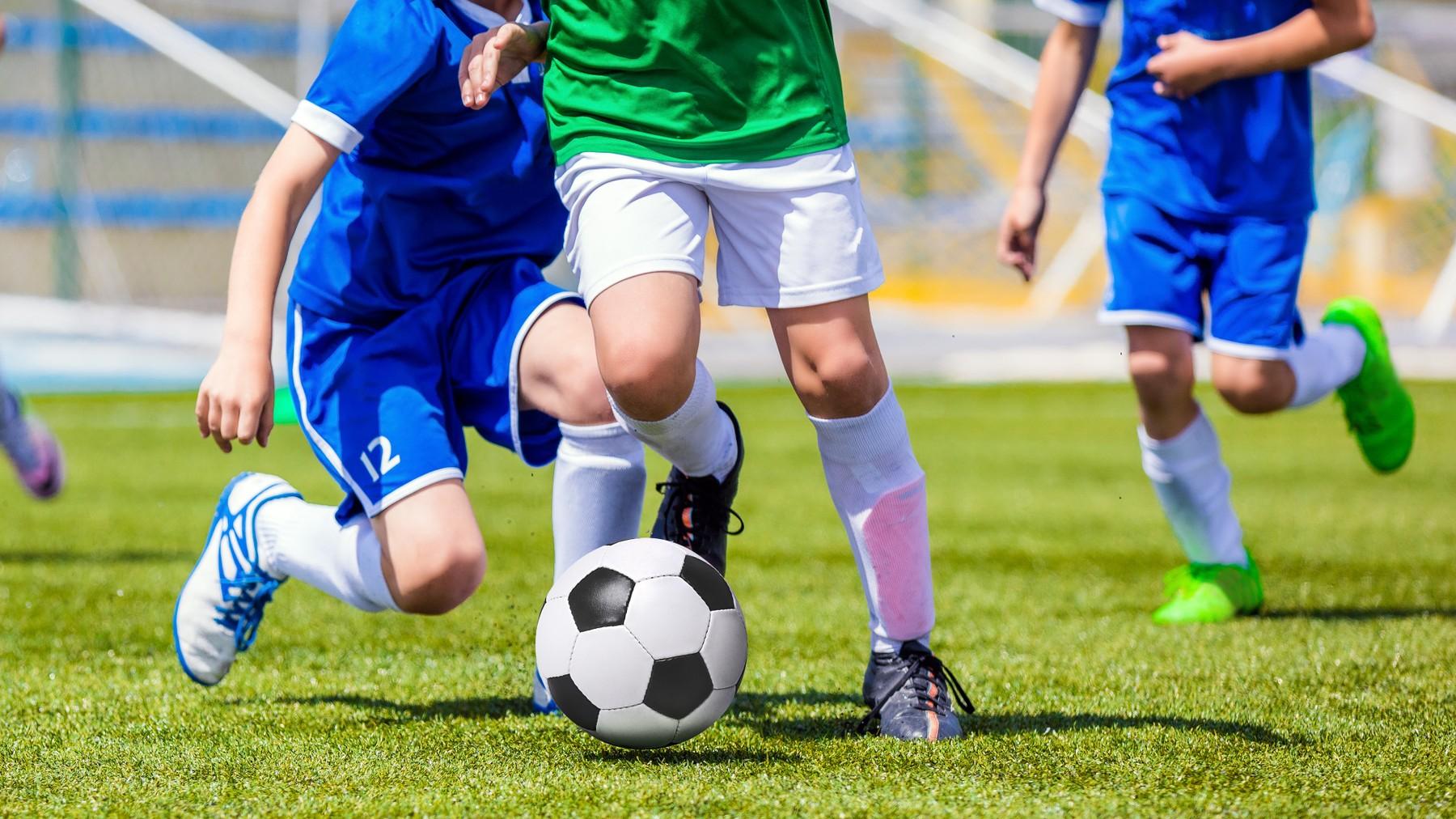 ขาของเด็กผู้ชายที่กำลังเตะบอลที่สนามที่มีหญ้าสีเขียว