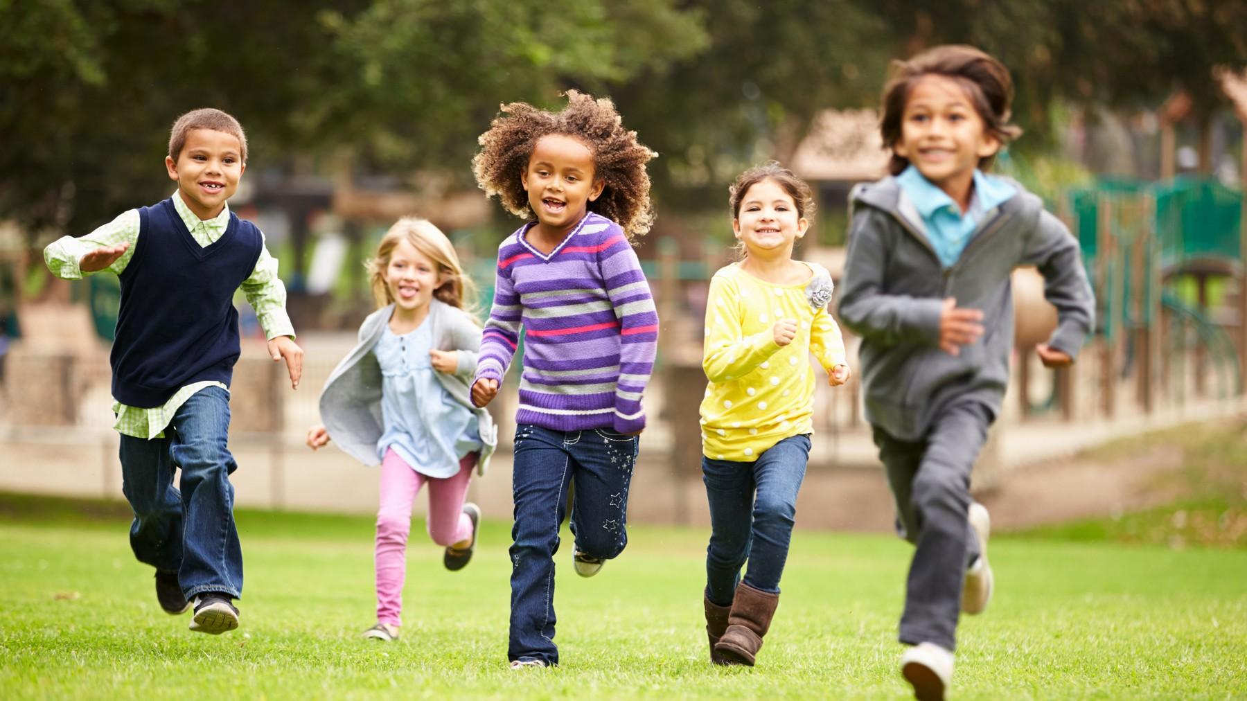 เด็กห้าคนกำลังวิ่งเล่นในสนามเด็กเล่น