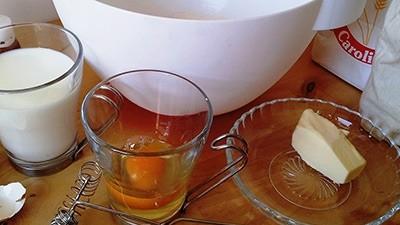 ภาชนะทั้งสามอันที่ถูกใส่ด้วยไข่เนยและนมวางอยู่บนโต๊ะสีน้ำตาล