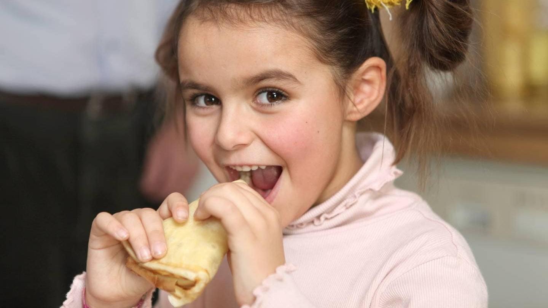 เด็กผู้หญิงมัดจุกสองข้างกำลังหยิบขนมเข้าปาก