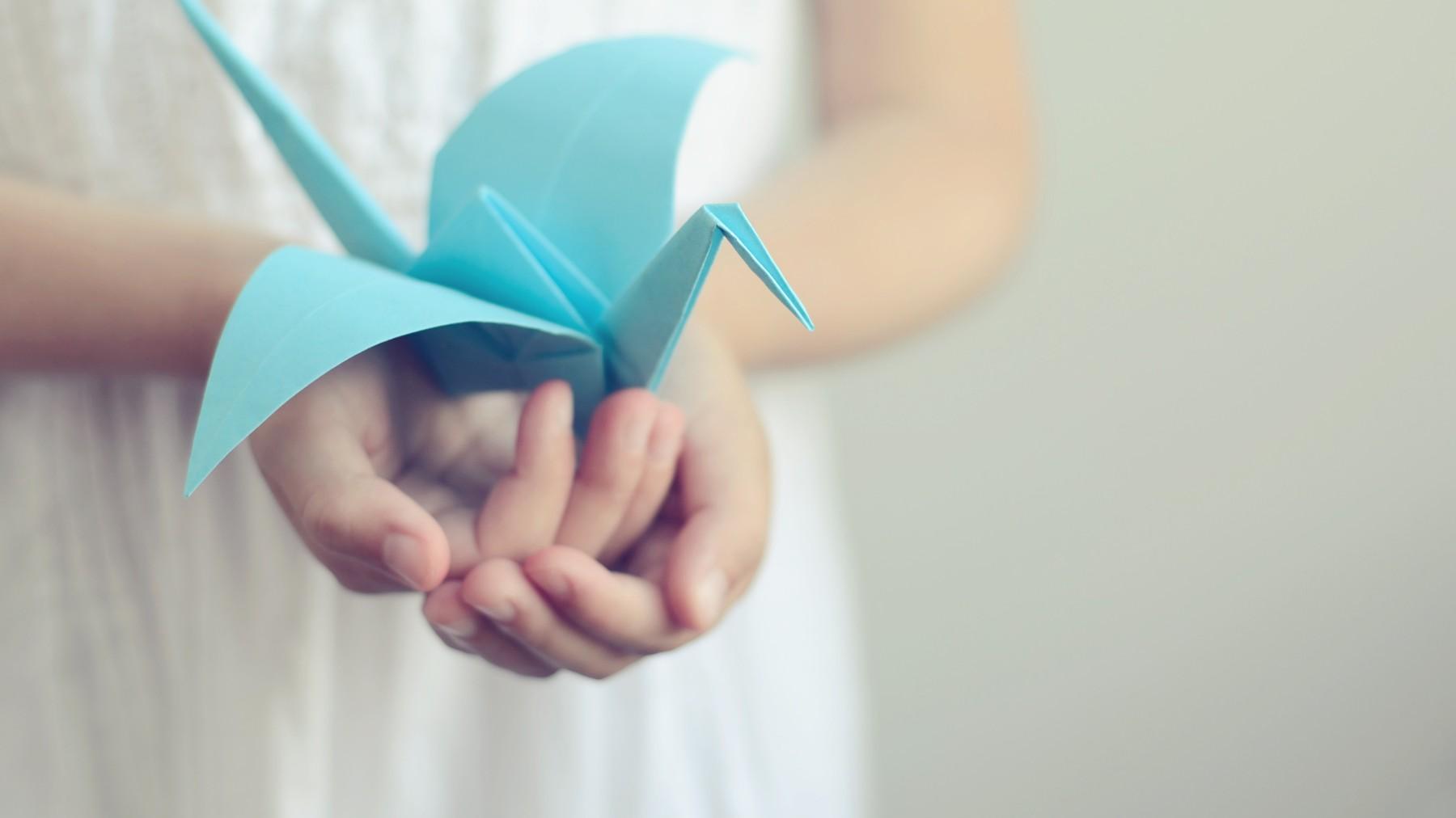 นกพับสีฟ้าบนมือที่ถืออยู่