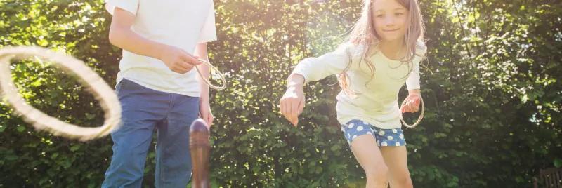 เด็กหญิงและเด็กชายกำลังเล่นโยนแหวน
