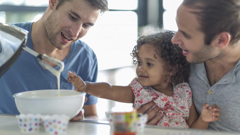 เด็กผู้หญิงถูกอุ้มโดยพ่อกำลังหัดทำขนมโดยกำลังตีแป้งเค้กสีครีม